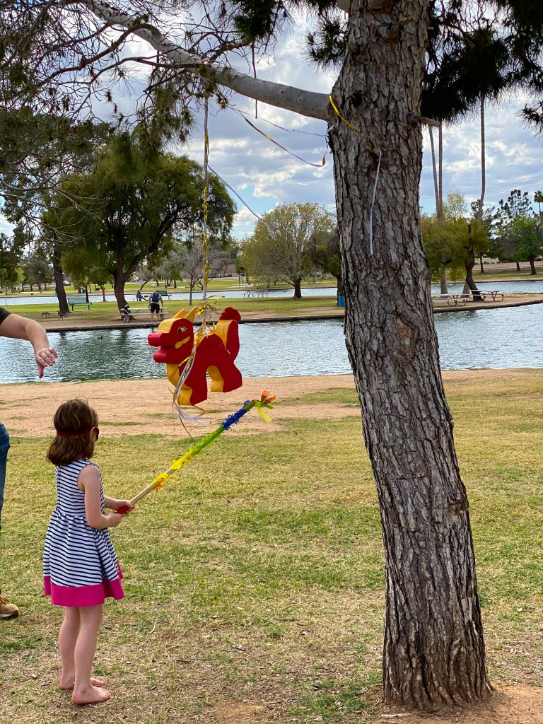 dragon pinata hanging from a tree with child blindfolded about to hit it.