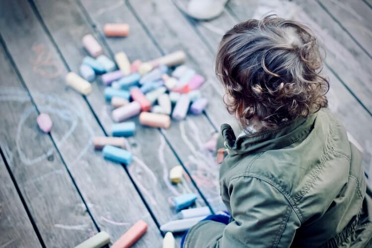 child looking at chalk on the floor