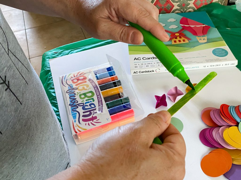 painting a wooden craft stick green with brush marker