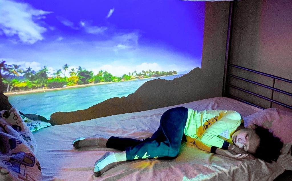 child sleeping with a projection of a beach