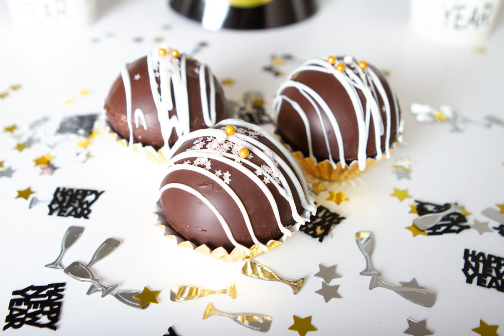 3 Cocoa Bombs surrounded by confetti
