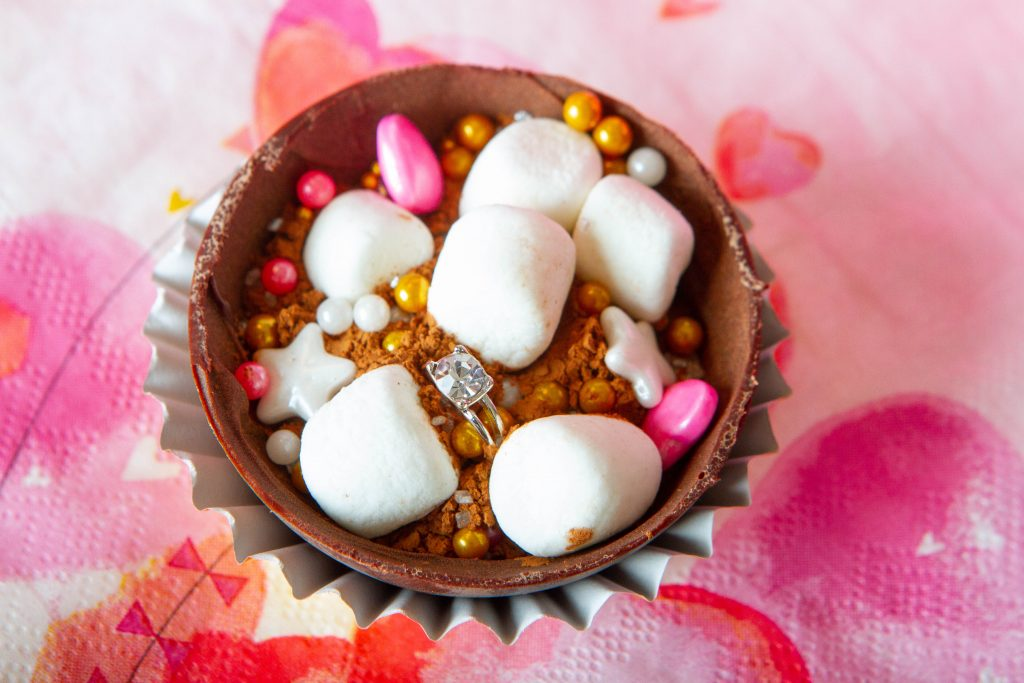 cocoa bomb with marshmallows, sprinkles and an engagement ring.