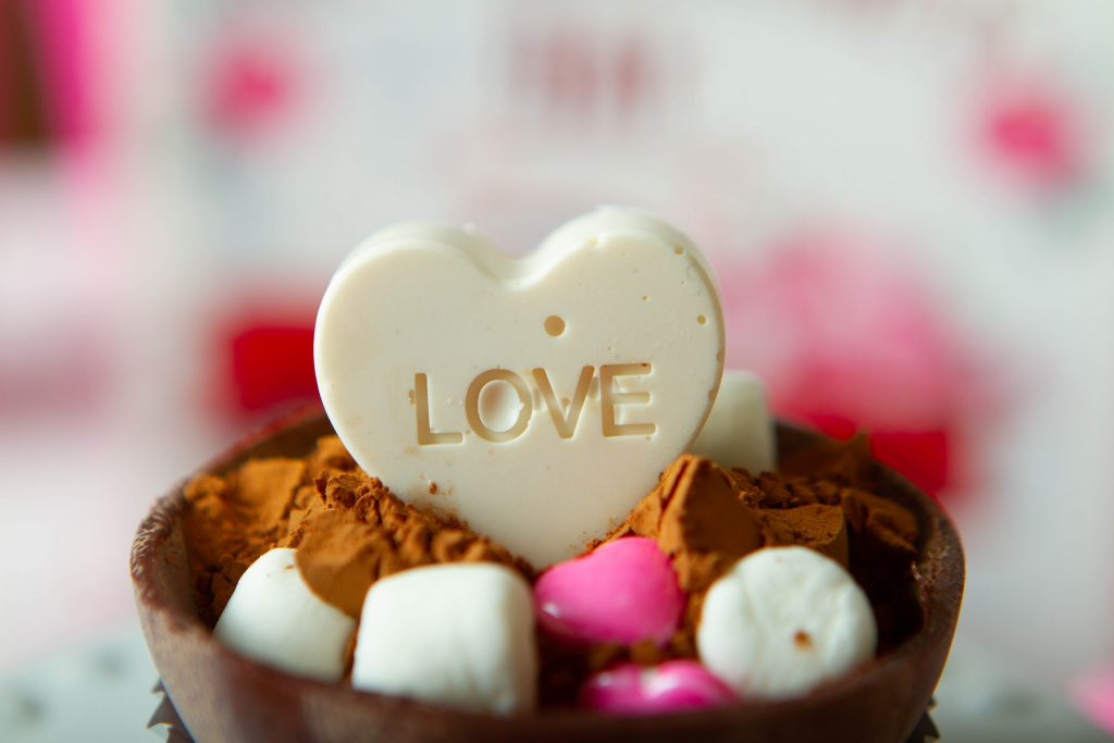 white candy melt heart that says love inside a cocoa bomb
