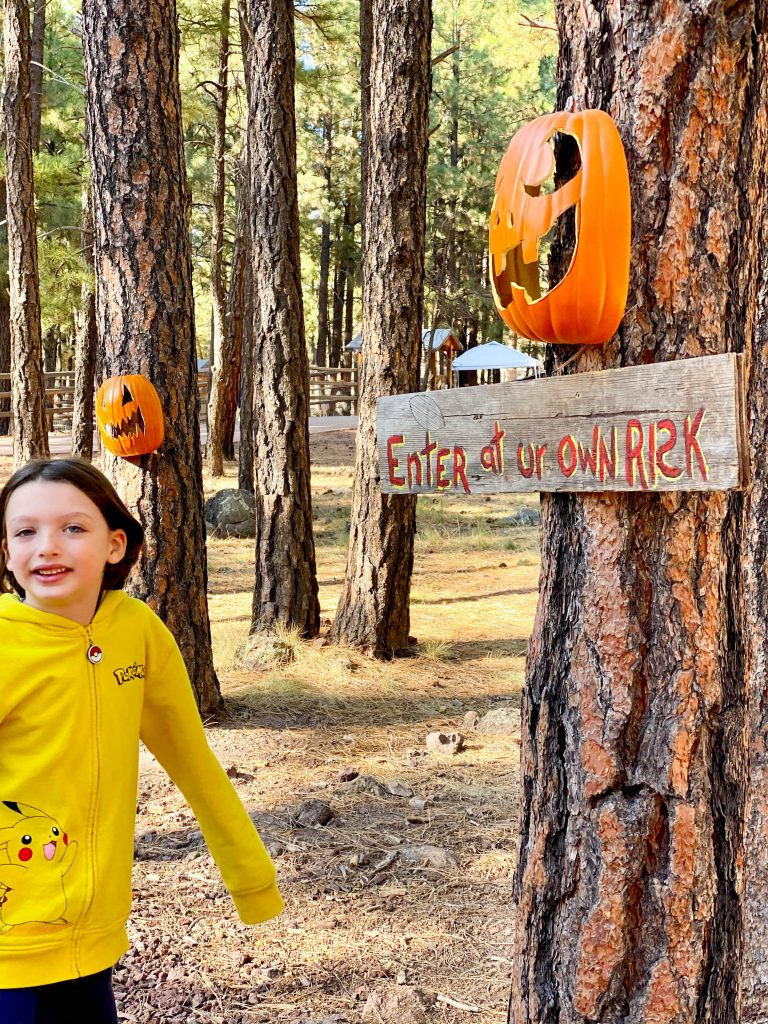 boy next to tree with sign that says enter at your own risk