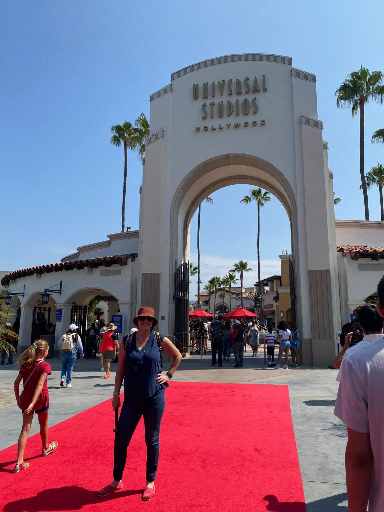 woman standing on red carpet at entrance of Universal Studios