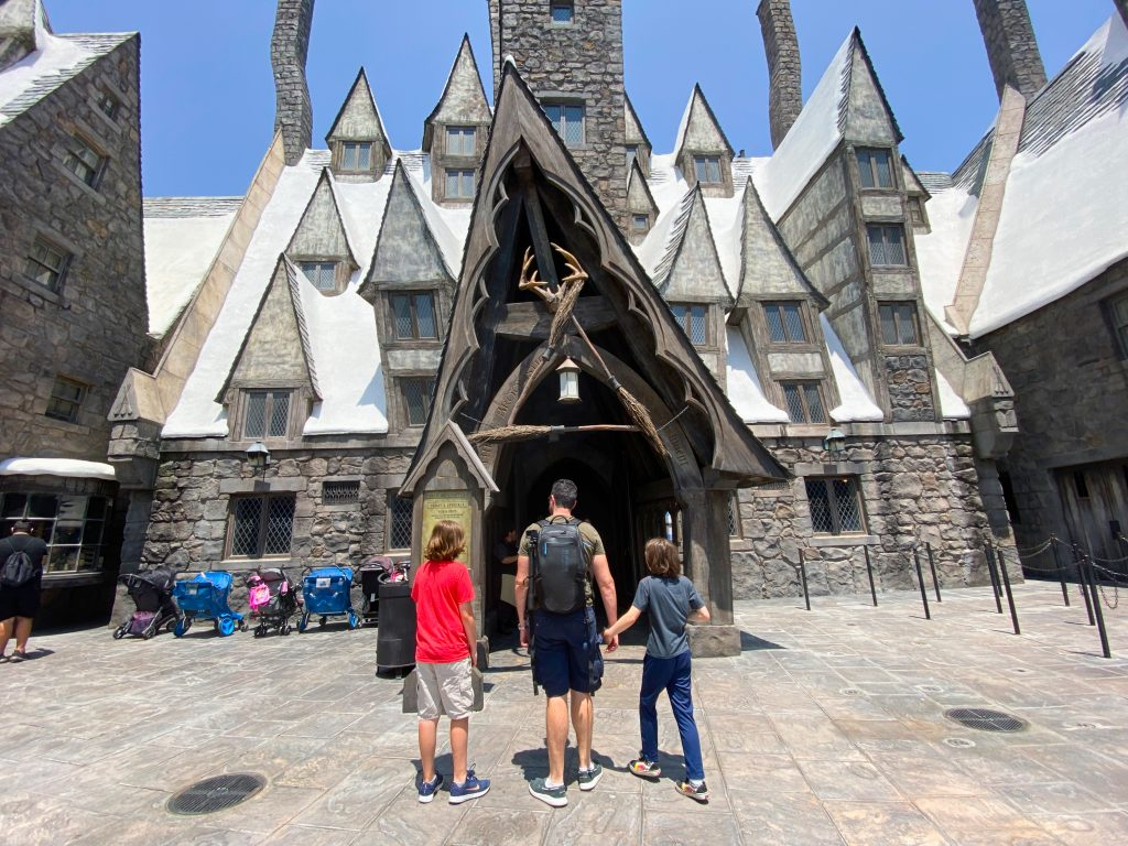 father and two boys walking into Three Broomsticks