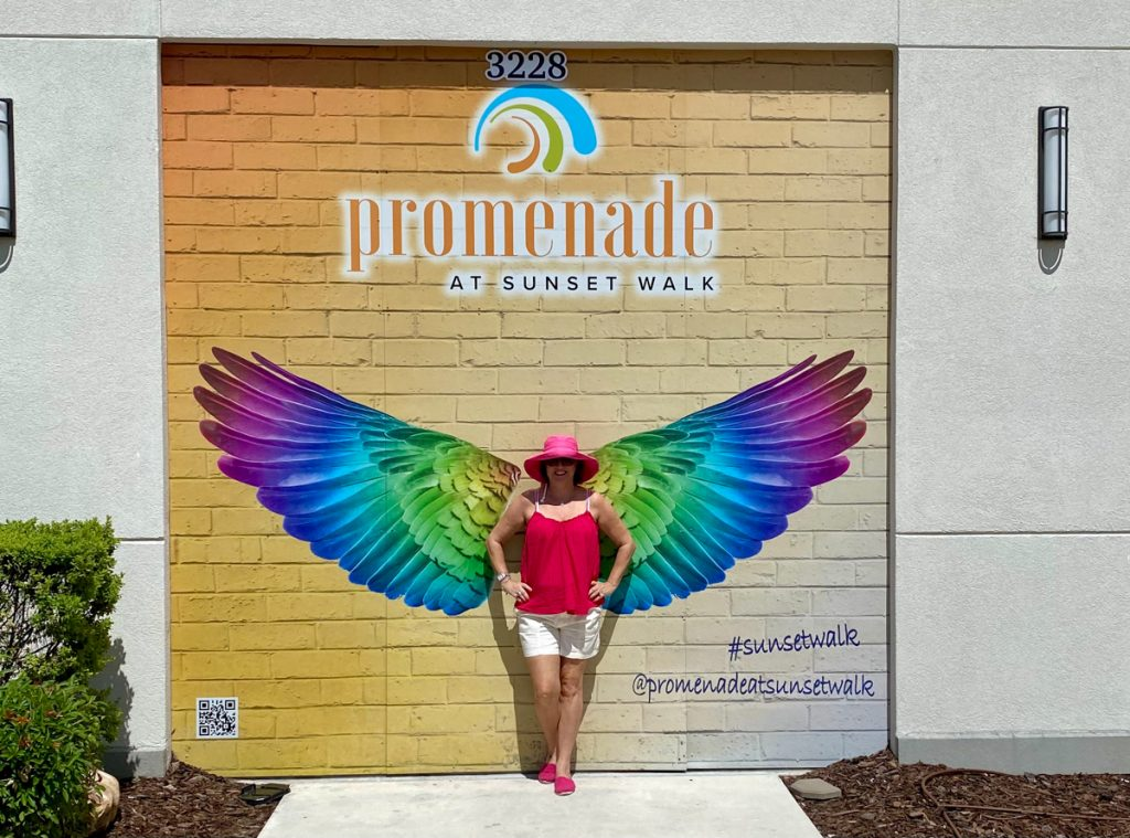girl standing in front of wings at Promenade at Sunset Walk