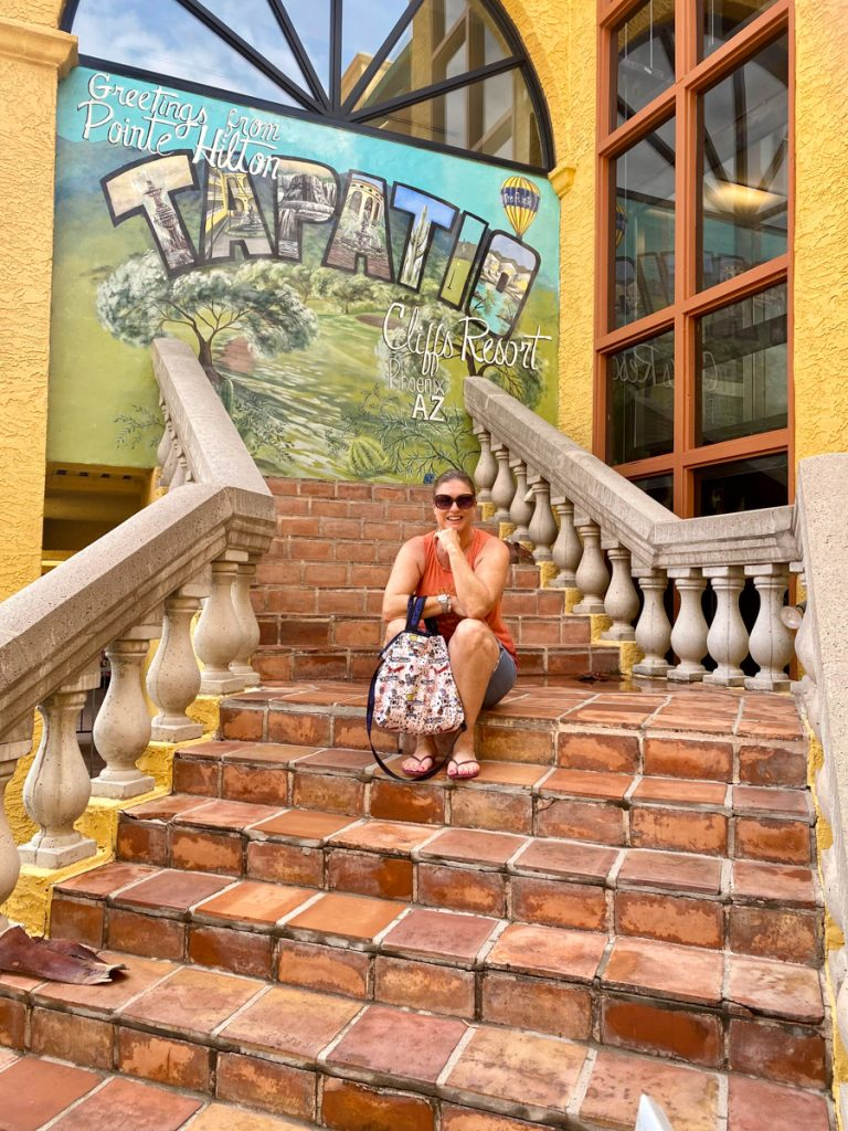woman sitting on stairs at The Pointe Hilton Tapatio Cliffs Resort