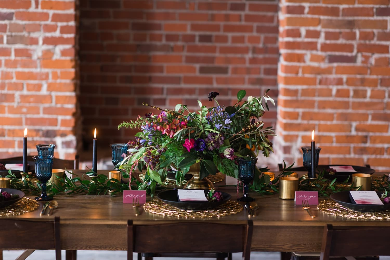 dark floral arrangement and farmhouse table wedding reception