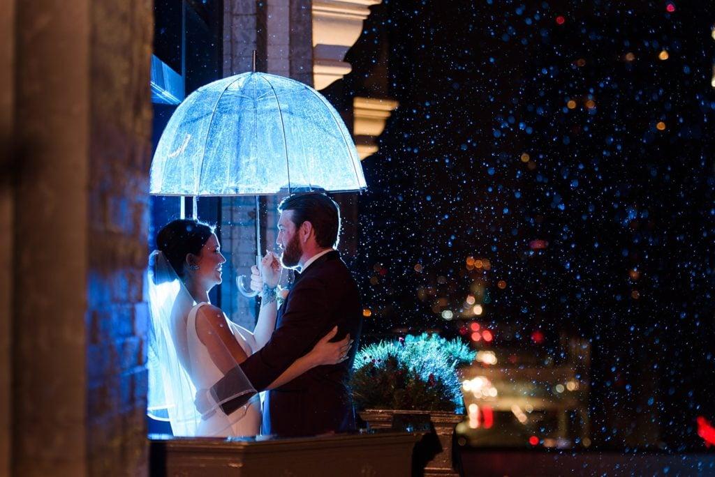 Des Moines tea room balcony bride and groom at night with umbrella