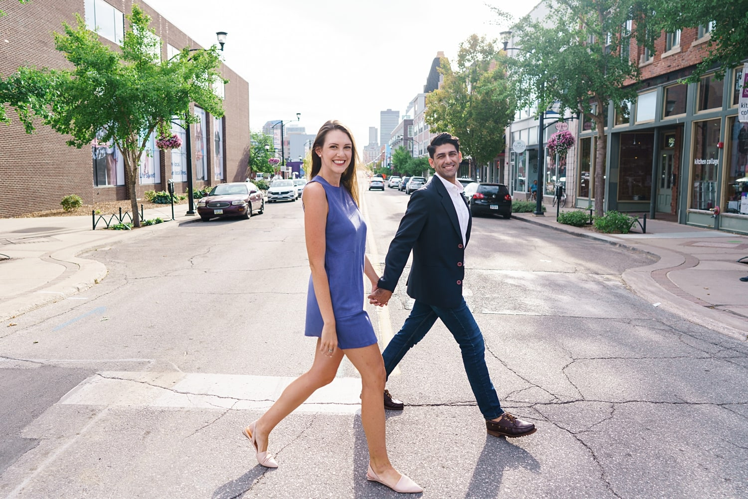 couple walking across the street for engagement photos holding hands