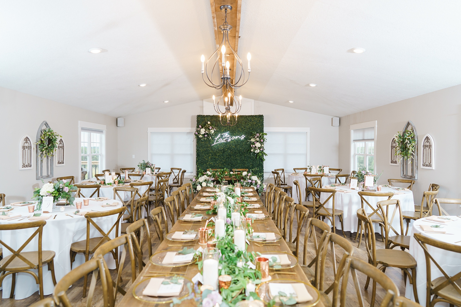 alta house wedding reception in newton iowa with greenery backdrop, farmhouse tables, and lavender and copper details
