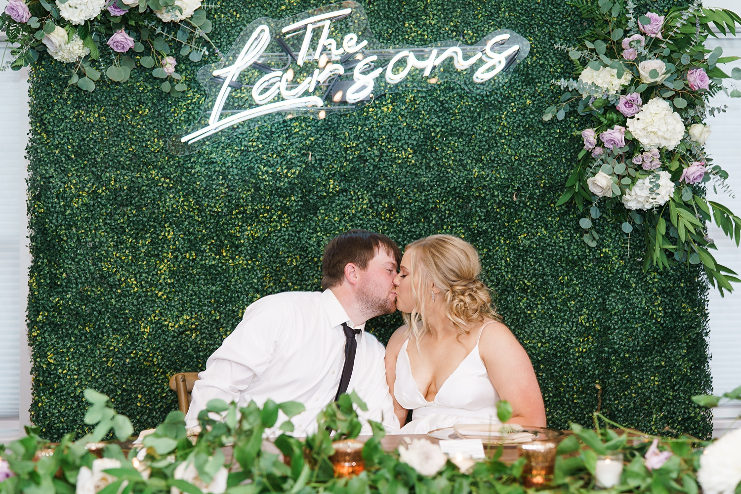 greenery backdrop with neon sign for wedding reception