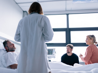 Doctor discussing with a patient in a hospital bed and family members. Source: iStock by Getty Images; Copyright: jacoblund; URL: https://www.istockphoto.com/ca/photo/female-physician-visiting-patient-in-hospital-room-gm852501710-140081373?clarity=false; License: Licensed by the authors.