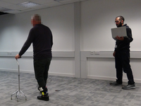 Image taken from one of the trials in the study reported in this paper. Image shows a stroke survivor with hemiparesis walking while wearing the haptic device. A researcher follows the participant attending for his safety and monitoring the data collection process. Source: Theodoros Georgiou; Copyright: The Authors; URL: http://biomedeng.jmir.org/2020/1/e18649/; License: Creative Commons Attribution (CC-BY).