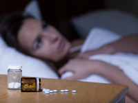 Sleeping pills lying on night table and woman trying to sleep. Source: Shutterstock; Copyright: Photographee.eu; URL: https://www.shutterstock.com/image-photo/sleeping-pills-lying-on-night-table-237699763; License: Licensed by the authors.
