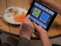 Resident and caregiver using a mobile app to support communication during mealtime. Source: Image created by the authors; Copyright: The Authors; URL: http://aging.jmir.org/2020/1/e17136/; License: Creative Commons Attribution (CC-BY).