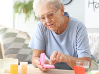 An older adult managing medications. Source: Shutterstock. Image created by Pixel-shot; Copyright: Jessica Ivo; URL: https://www.shutterstock.com/image-photo/elderly-woman-medicines-home-1533576182; License: Licensed by the authors.