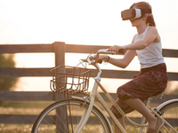 Using VR to promote physical activity in adolescents and trying to carry over the effects to the real world. Source: Pexels; Copyright: Sebastian Voortman; URL: https://www.pexels.com/photo/girl-wearing-vr-box-driving-bicycle-during-golden-hour-166055/; License: Licensed by the authors.