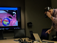 A user is manipulating an augmented reality model using the Hololens which is also being projected to a television screen. Source: Image created by the authors; Copyright: The Authors; URL: http://periop.jmir.org/2020/2/e18367/; License: Creative Commons Attribution (CC-BY).