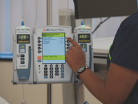 Nurse programming a smart pump and receiving a warning from the Dose Error Reduction System. Source: BD Media Beacon; Copyright: James Waterson; URL: http://humanfactors.jmir.org/2020/3/e20364/; License: Ownership of image given by Medical Affairs Department, BD.