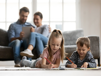Young family with parents reading online material. Source: iStock by Getty Images; Copyright: fizkes; URL: https://www.istockphoto.com/photo/little-siblings-lying-on-floor-painting-at-home-gm1201510261-344601516; License: Licensed by the authors.