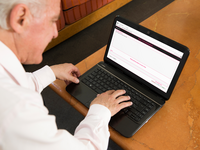 Older Adult using Manage Your Life Online (MYLO). Source: The Authors/ PlaceIt; Copyright: The Authors / PlaceIt; URL: https://placeit.net/c/mockups/stages/elderly-man-with-hp-laptop-at-home; License: Licensed by the authors.