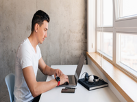 Source: freepik; Copyright: marymarkevich; URL: https://www.freepik.com/free-photo/young-handsome-smiling-man-casual-outfit-sitting-table-working-laptop-staying-home-alone_9699668.htm#page=1&query=person%20using%20computer&position=28; License: Licensed by JMIR.