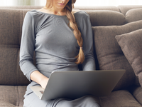 Source: freepik; Copyright: shurkin_son; URL: https://www.freepik.com/free-photo/cropped-shot-young-blond-woman-with-braid-working-laptop-sitting-comfortable-dark-sofa-home-backlit-warm-light-freelance-lifestyle-concept_11193327.htm#page=2&query=person+relaxing+with+laptop&position=42; License: Licensed by JMIR.