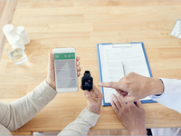 Doctor demonstrating health app with patient. Source: iStockphoto; Copyright: Dragonimages; URL: https://www.istockphoto.com/gb/photo/discussing-daily-actitivty-with-doctor-gm872291754-243652375?clarity=false; License: Licensed by the authors.