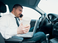 Driver talking on a mobile phone while drinking coffee and working on a laptop. Source: iStock by Getty Images; Copyright: tommaso79; URL: https://www.istockphoto.com/ca/photo/stressed-businessman-working-seated-in-car-gm903701712-249237902; License: Licensed by the authors.