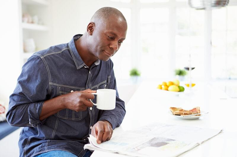 man with coffee reading paper