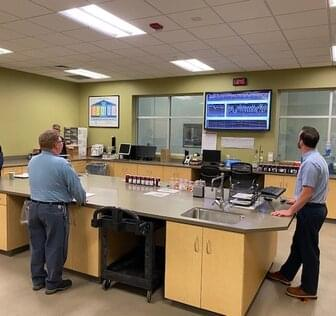 Workers reviewing monitor in shared room
