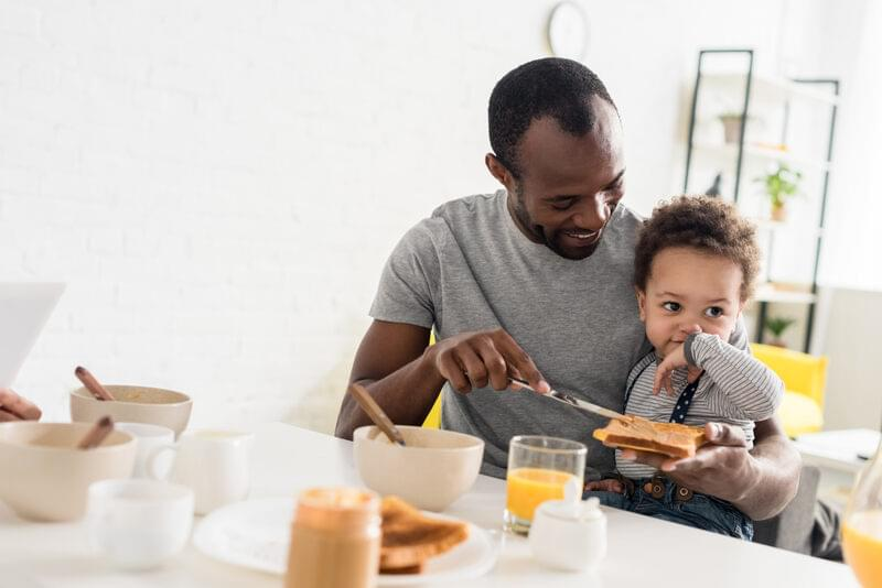 Man making peanut butter toast for toddler