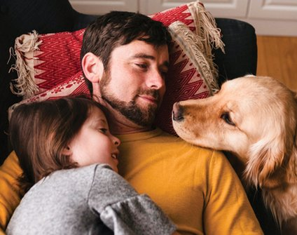 Father and daughter with dog on couch