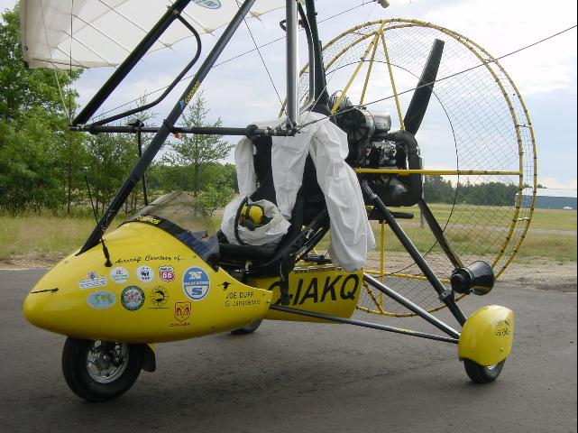 Ultralight airplane parked, with pilot's costume hanging over seat.