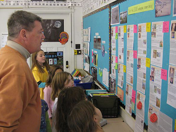 Pilot Joe Duff and second graders look at Journey North's crane bio pages on a shool visit.
