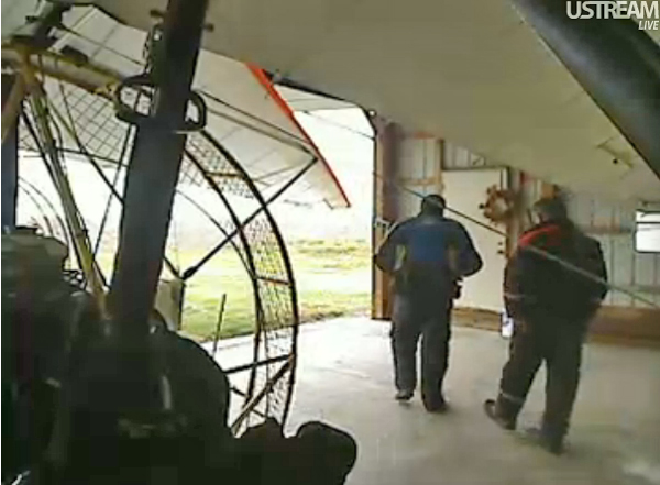 Two pilots wait in the hangar for the test trike pilot to return with a verdict.