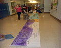 Students making a giant gray whale poster on the hallway floor.