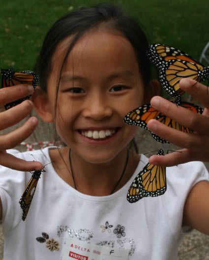 Girl with tagged monarch butterflies.