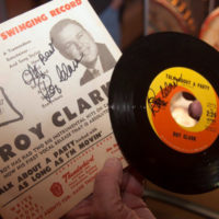 Roy Clark with a signed poster and 45 RPM single at the American Banjo Museum