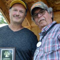 Brian Paige accepts his father, Ralph's, SMBMA Hall of Honor induction from Bill Warren at the 2017 Milan Bluegrass Festival