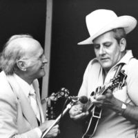 John Duffey with Bill Monroe, wearing Monroe's hat and playing his F-12 - photo by Ron Petronko