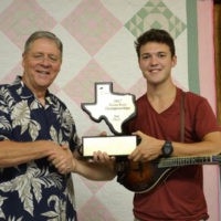 Texas Mandolin Champion for 2017 Sam Armstrong accepts his trophy from Arvin Holland with BABA - photo by Tina Boatwright