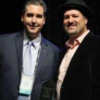 Darin Aldridge accepts his Mentor Momentum award from Stephen Mougin during World of Bluegrass - photo by Frank Baker