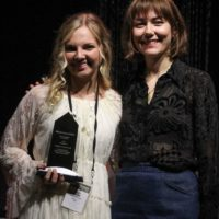 Carly Arrowood accepts her Instrumentalist Momentum award from Molly Tuttle during World of Bluegrass - photo by Frank Baker