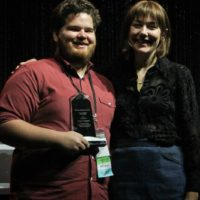 Casey Campbell accepts his Instrumentalist Momentum award from Molly Tuttle during World of Bluegrass - photo by Frank Baker