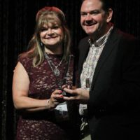 Cindy Baucom and Joe Mullins accepting the 2017 Broadcaster of the Year Award from the IBMA - photo by Frank Baker