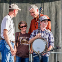 Riley Gilbreath with his parents as Steve Huber presents him with a new Huber Workhorse banjo - photo by Nathaniel Dalzell