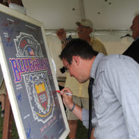 Everyone signs the poster at the 2018 Red, White & Bluegrass Festival - photo by Laura Tate Photography